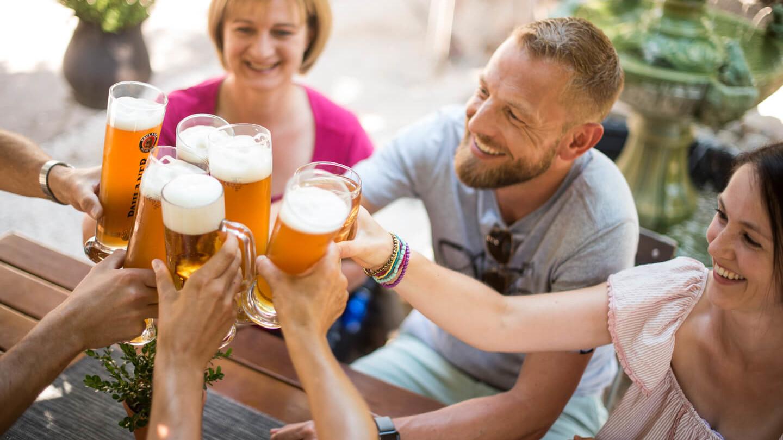"""Biergarten des Restaurants """"Zum  Pferchtal"""" in Lautzkirchen, Grupp stößt mit Biergläsern an"""