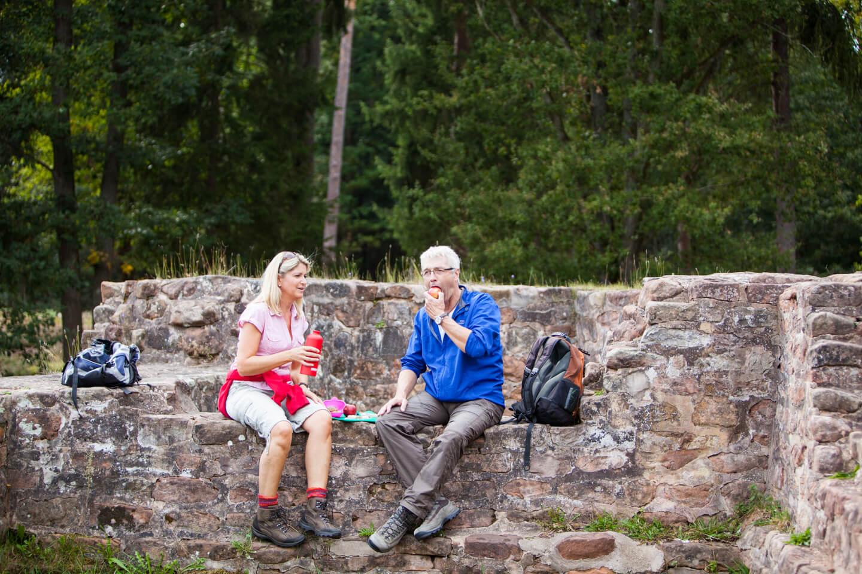 Wanderer machen auf Ihrer Wanderung durch den Bliesgau eine Rast auf einer Mauer
