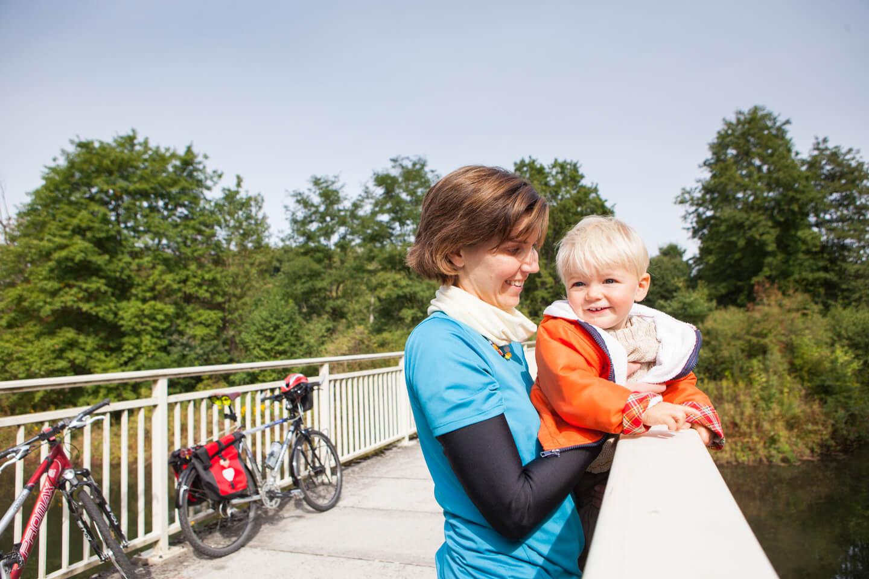 Familie macht eine Rast bei einer Radtour auf einer Brücke