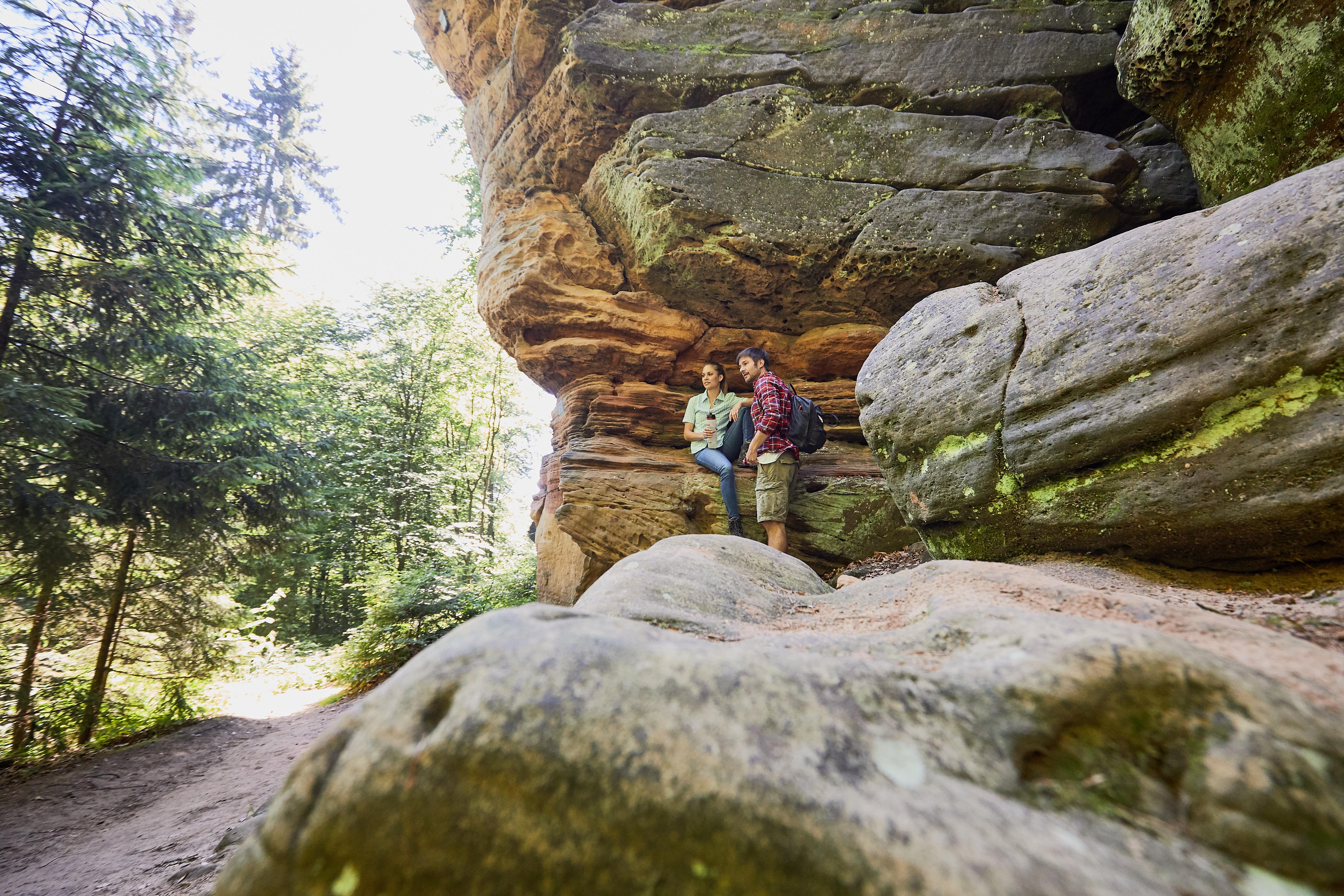 Wanderer am Unglücksfelsen auf dem Kirkeler Felsenpfad